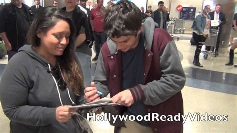 Dylan O'Brien greets fans arriving back at LAX Airport in